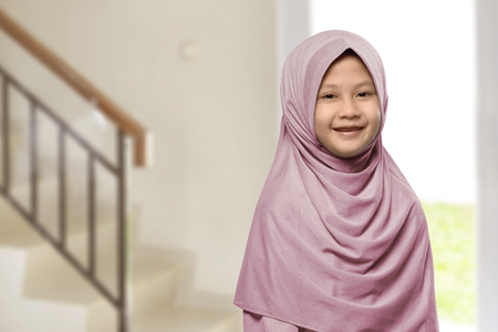 Little asian muslim girl with hijab at home
