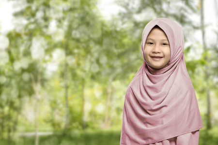 petite fille musulmane: Cheerful asian muslim woman wearing hijab standing in the park