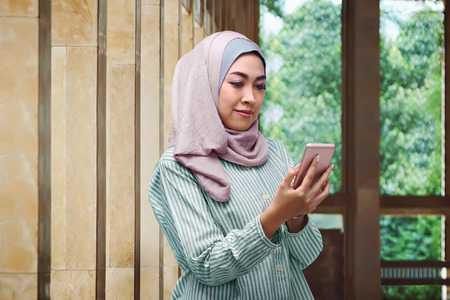 head scarf: Pretty asian muslim woman with veil holding mobile phone at indoor