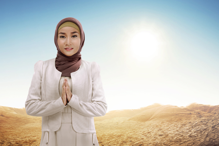 Young asian muslim woman in hijab with smiley face standing at desert Stock Photo