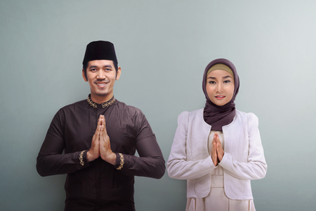 Asian muslim man and woman with traditional dress praying together over grey background Foto de archivo