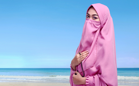 Portrait of asian muslim woman with niqab holding prayer beads on the beach