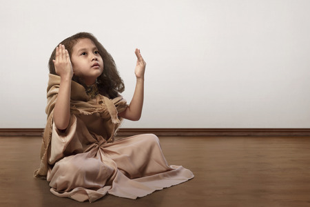 Portrait of asian muslim kid sitting on floor and praying inside the room