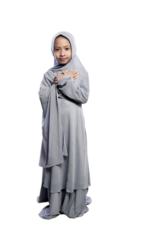 petite fille musulmane: Portrait of asian muslim child wearing hijab standing isolated over white background Banque d'images