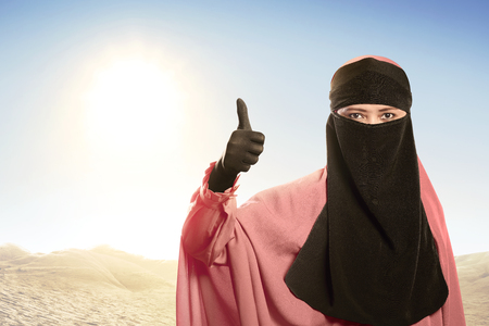 Cheerful asian muslim woman wearing hijab with good sign against sunlight background Stock Photo