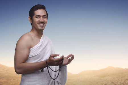 Happy asian muslim man wearing ihram clothes and prayer beads ready for hajj
