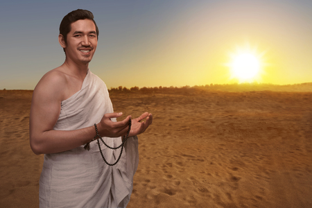 Handsome asian muslim man in ihram dress with prayer beads ready for hajj