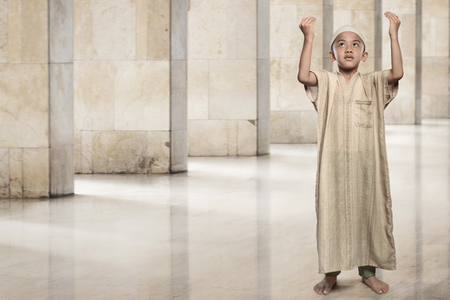Little asian muslim boy raising hand and praying on the mosque