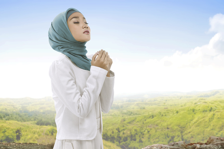 Pretty asian muslim woman wearing hijab raising hand and praying with landscape view background