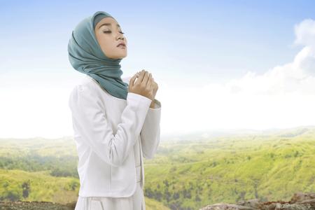 Mooie Aziatische moslimvrouw die hijab draagt, hand en bidden met landschapskijk achtergrond