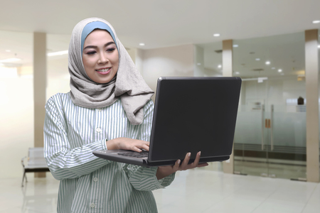 outerwear: Young asian muslim woman using laptop while standing in the office room
