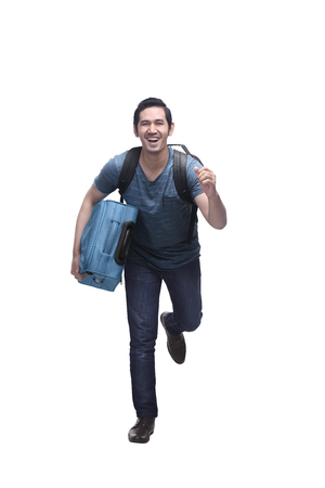 Attractive asian travelling man with suitcase running isolated over white background Stockfoto