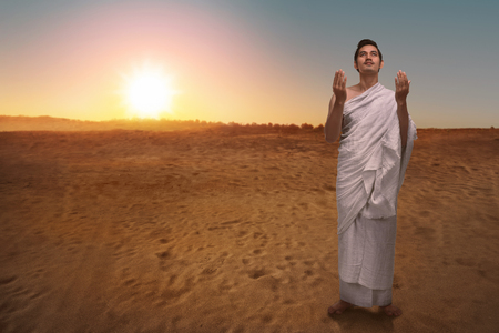 Religious asian muslim man in ihram praying to god with desert view background Reklamní fotografie