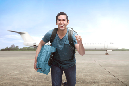 Young asian travelling man get off the plane with suitcase on the landing strip