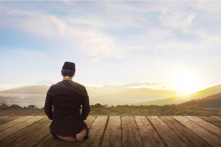 Portrait of muslim man kneeling and praying to god with landscape view background