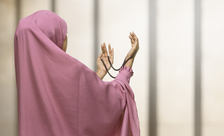 religious clothing: Pretty asian muslim woman wearing raising hand and praying in the mosque