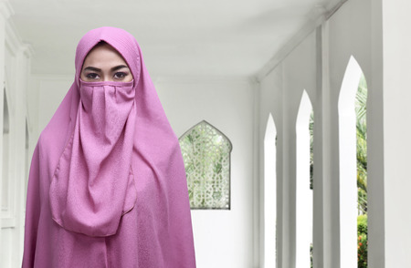 Young asian muslim woman wearing niqab traditional veil inside the mosque