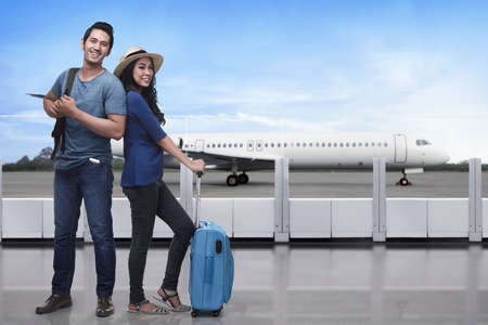 Portrait of asian tourist couple with backpack and suitcase standing against airplane background