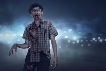 Aggressive spooky asian zombie man walking with streetlight background Stock Photo