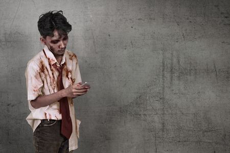 Scary asian zombie man holding cellphone over dirty wall background