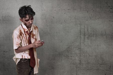 Scary asiatischen Zombie Mann mit Handy über schmutzigen Wand Hintergrund Standard-Bild - 84423456