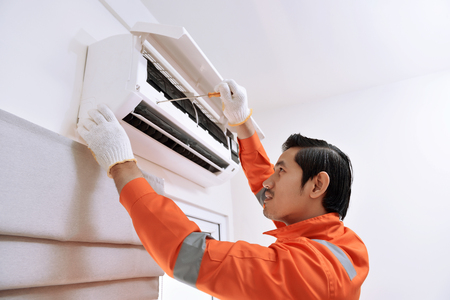 Young asian male technician repairing air conditioner with screwdriver at home
