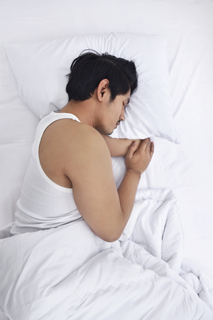 Handsome asian man sleep tightly in his bedroom