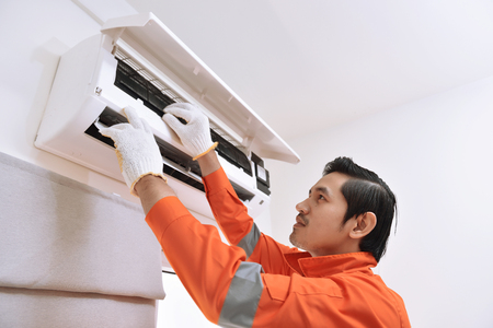 Young asian male technician repairing air conditioner at home Stockfoto