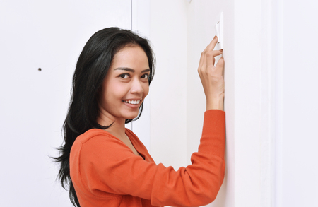 Beautiful asian woman turning off the light with wall switch in the home