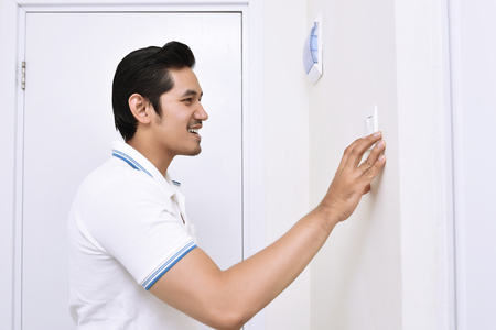 Handsome asian man turning off the light with wall switch in the home