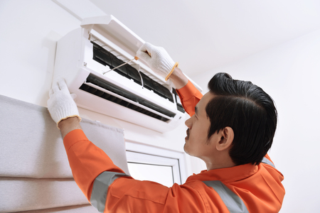 Young asian male technician repairing air conditioner with screwdriver at home Banco de Imagens - 85191925
