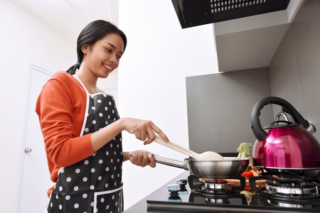 Smiling asian woman using frying pan and cooking in the kitchen Stok Fotoğraf