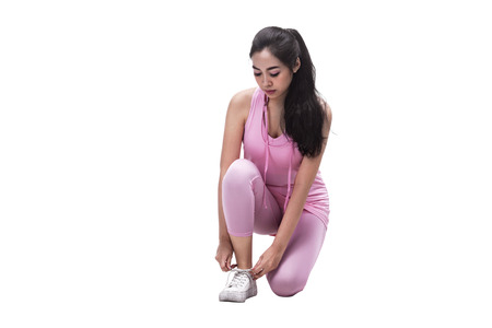 Young asian woman lacing her shoes before running isolated over white background