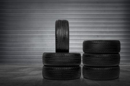 grooves: Stack of car tires over metal roller shutter background