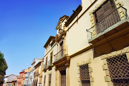 windows: Classic apartment buildings with balcony and colorful paint wall along the street in Spain