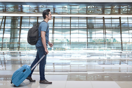 windows: Young asian man walking and pulling the suitcase in airport