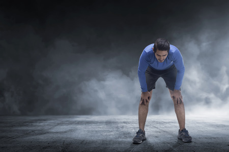 Young asian runner man taking rest from jogging on the concrete floor Stock Photo
