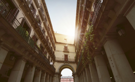 windows: Corridor between of the ancient buildings with gateway arch at sunshine in Spain Stock Photo