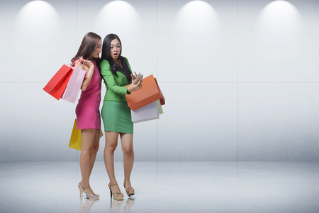 Surprised two asian woman with shopping bag when looking on smartphone against white wall background
