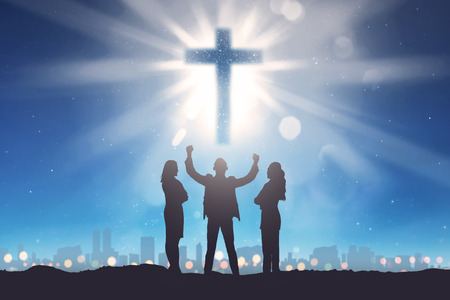 Silhouette of three people looking christian cross on the sky. Religion concept