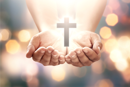 Human hand with shape cross in open palm over blur background
