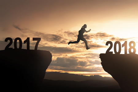 Silhouette of woman jump toward 2018 with sunset background