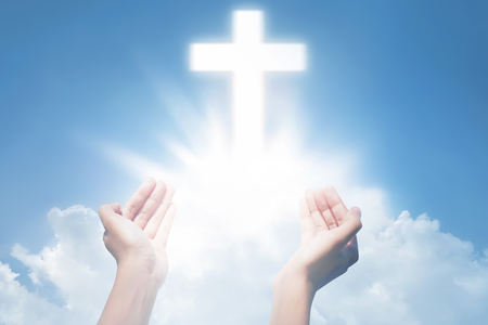 Human hands open palm and praying with cross on the sky background