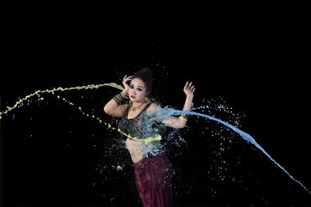 Exotischer asiatischer Bauchtänzerin , der mit bunter Farbe gegen schwarzen Hintergrund tanzt Standard-Bild - 90326835