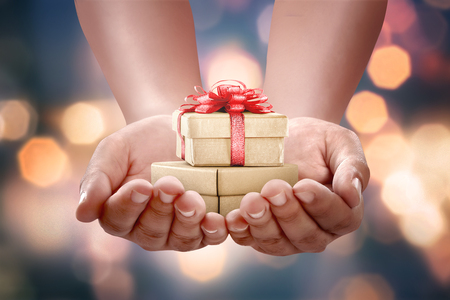 Human hands holding gift box for boxing day with blurred background. Boxing Day Concept