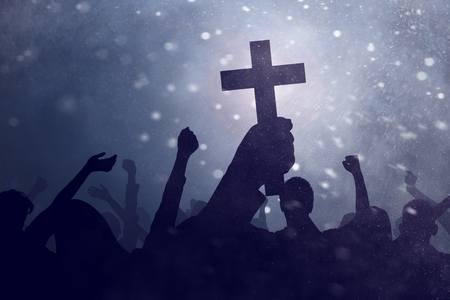 キリスト教の十字架を持つシルエットの手のイメージ、人々の背景
