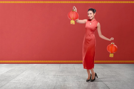 Young chinese woman in a traditional clothing holding red lanterns with red wall background