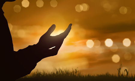Silhouette of human hand with open palm praying to god at sunset background