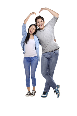 Portrait of asian couple making heart shape with hands posing isolated over white background Stock Photo