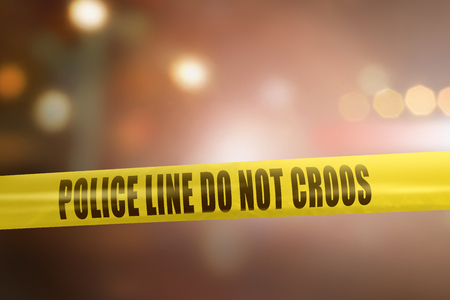 Yellow police line tape sign for protection crime scene with blurred light background